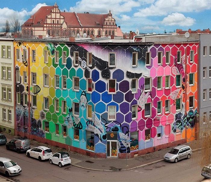 Un gigantesco alveare arcobaleno avvolge un palazzo a for Mural on building