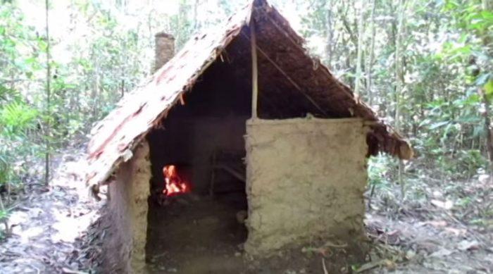 uomo-costruisce-capanna-rifugio-bosco-con-mani-nude