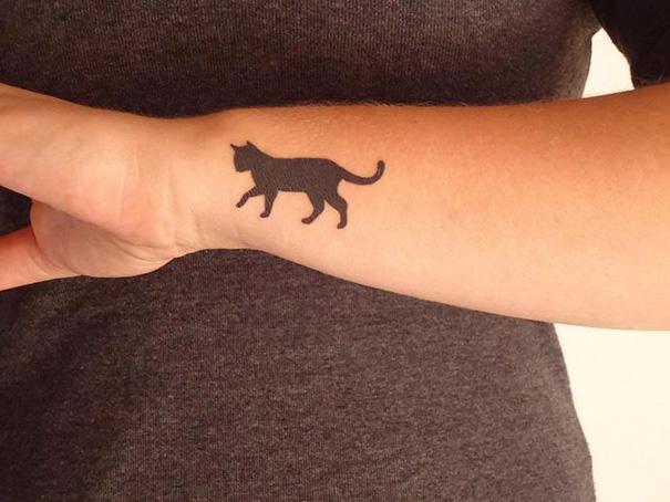 Tatuaggi gatti minimal, esempio sul braccio