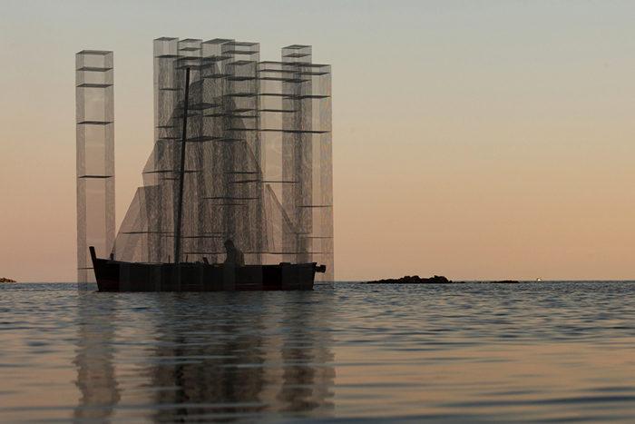 Una barca a vela in filo metallico risplende nella baia di Sapri