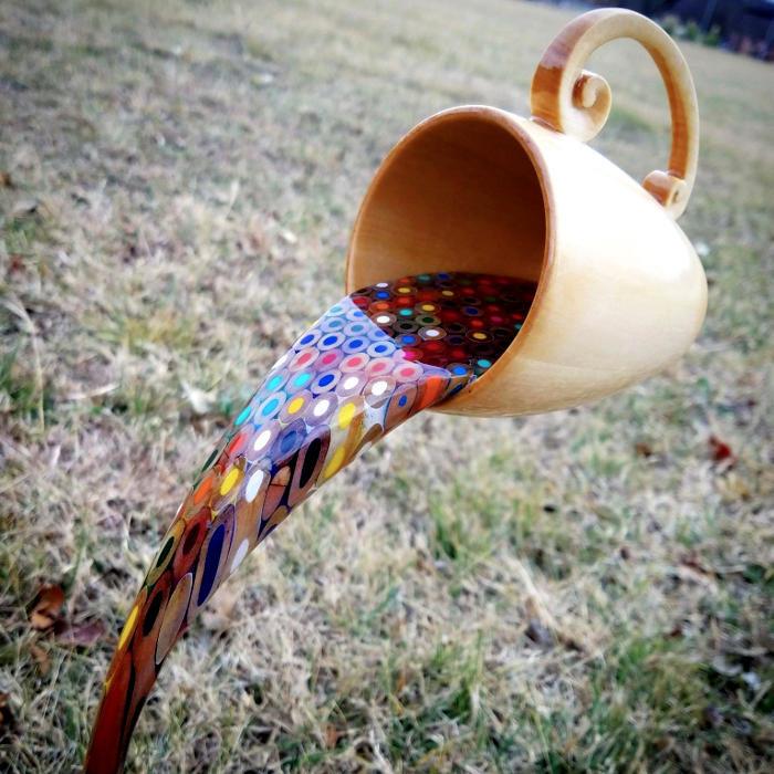 Una tazza fluttuante che versa un arcobaleno di matite colorate