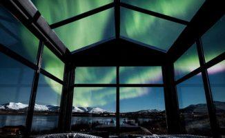 Una camera da letto con pareti e soffitto di vetro per ammirare l'aurora boreale