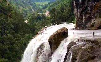 Camion pieno di persone attraversa una delle strade più pericolose del mondo inondata da una cascata