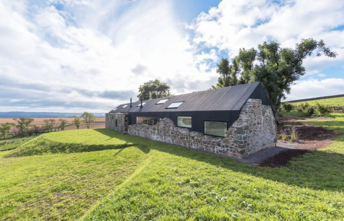 Una casa moderna costruita nelle rovine antiche di una fattoria