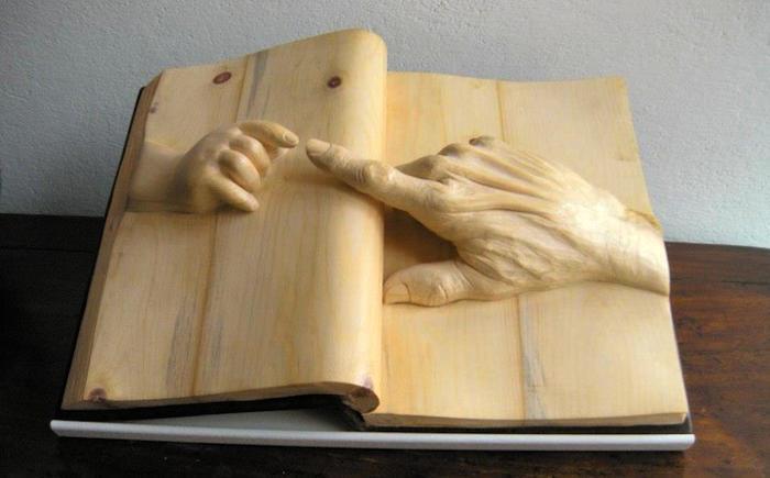 Mondi immaginari rinchiusi all'interno di libri scolpiti in legno