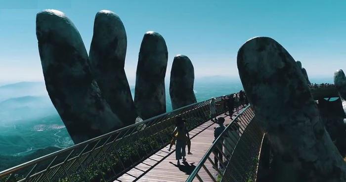 In Vietnam due mani giganti sollevano un ponte verso il cielo