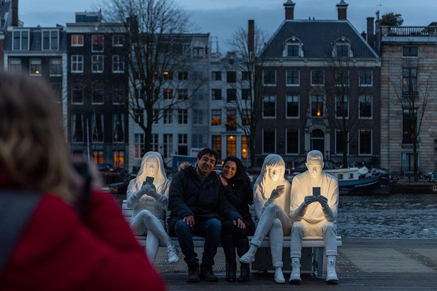 Amsterdam Light Festival scultura di persone che guardano lo smartphone