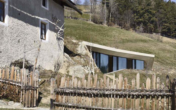In Alto Adige un'abitazione rurale è ampliata con una moderna casa sotterranea con prato verde sul tetto