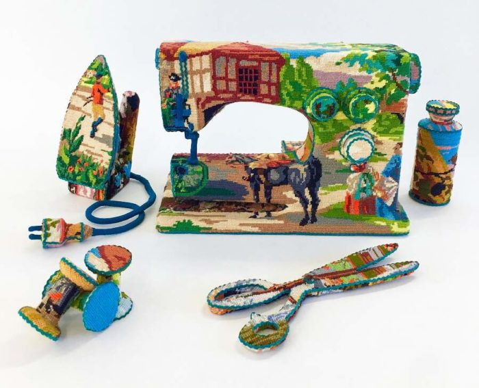 Vecchi oggetti di casa avvolti con ricami punto croce dall'artista Ulla Stina-Wikander