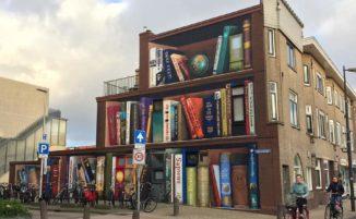 Street artist trasformano palazzina in una gigantesca libreria con le letture preferite degli abitanti
