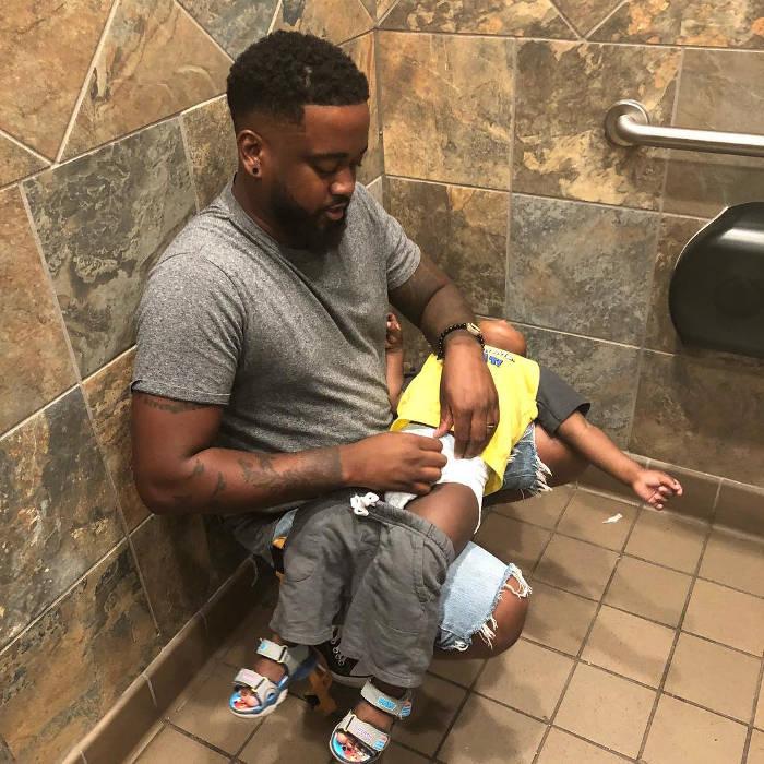 La foto di un papà che cambia il pannolino del figlio nel bagno degli uomini diventa virale e Pampers installa dei fasciatoi