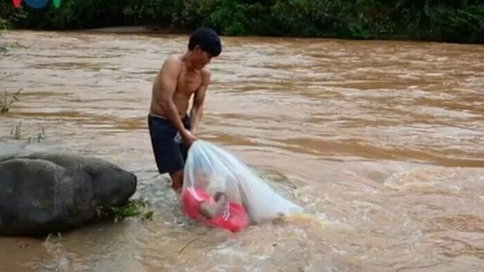 Bambini attraversano un fiume in sacchetti di plastica per andare a scuola in un villaggio del Vietnam