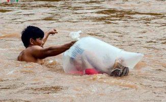 Bambini in sacchetti di plastica per attraversare un fiume e andare a scuola in questo villaggio del Vietnam