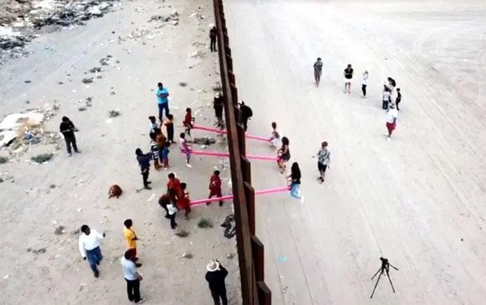 Bambini americani e messicani giocano insieme su altalene rosa sul muro di confine alla faccia di Trump