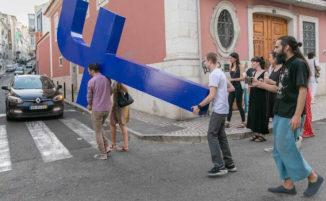 """Artista trascina la """"croce"""" di Facebook per le strade di Lisbona"""