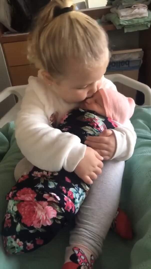 Bambina di 3 anni tiene in braccio la sorellina neonata per la prima volta, ed è amore