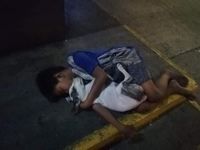 Bambino senzatetto dorme abbracciando il suo cane nell'indifferenza dei passanti