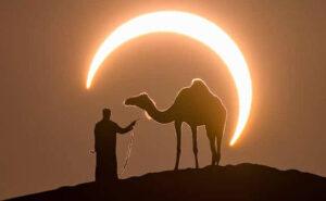 Foto dal tempismo perfetto raccoglie un uomo e il suo cammello in un'eclissi solare